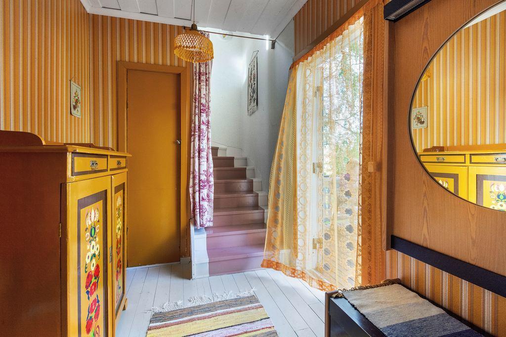 Hall men trapp till övervåningen, förråd under trappan.