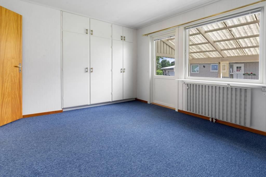 Master bedroom med heltäckningsmatta och tillgång till altan.