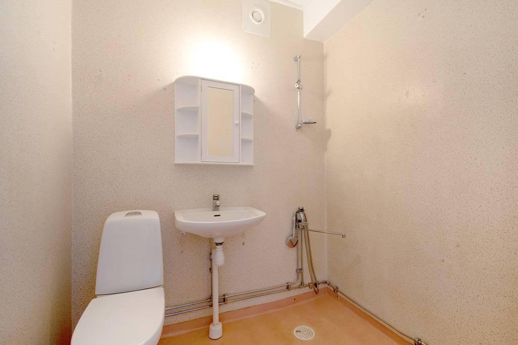 Badrum med våtrumsmatta och våtrumstapet.