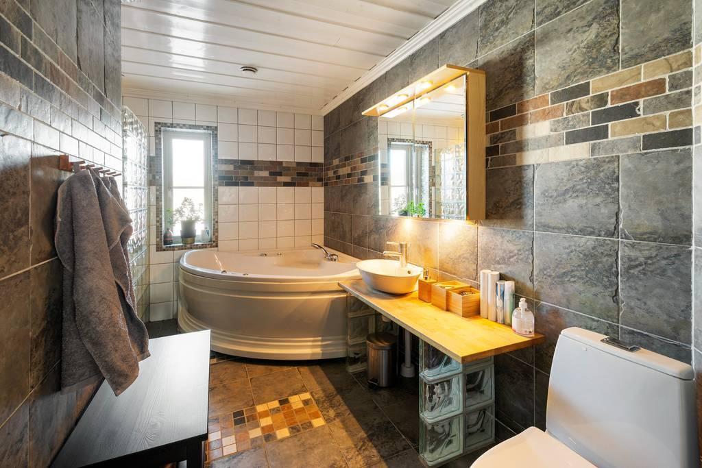 Badrum i kakel och klinker. Här finns både badkar och stor överhängd dusch.