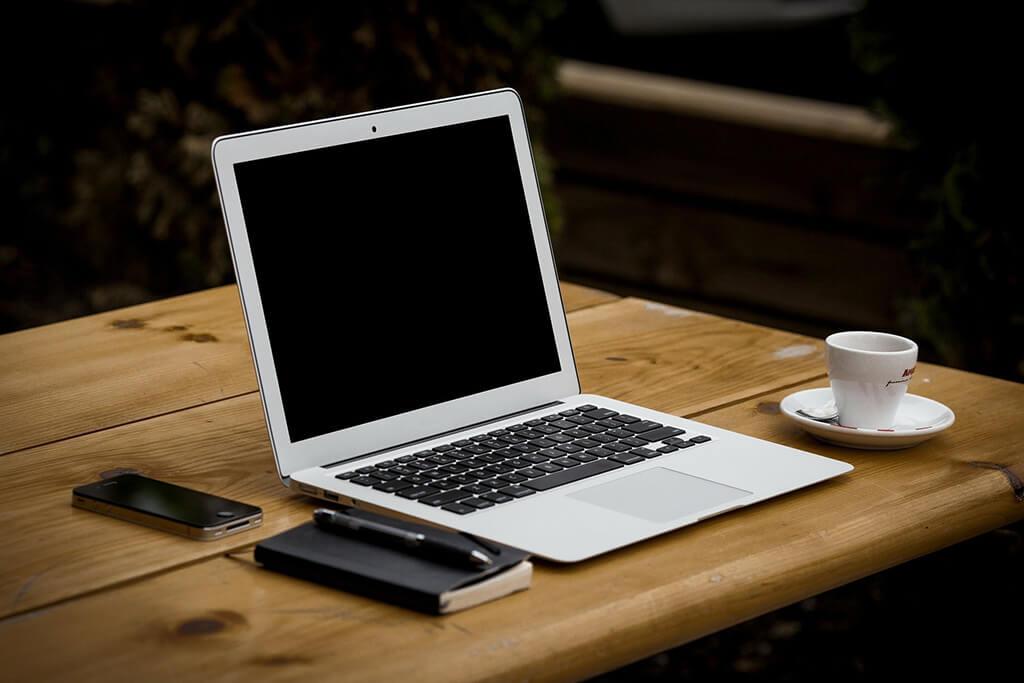 Dator, mobil på skrivbord med kaffekopp